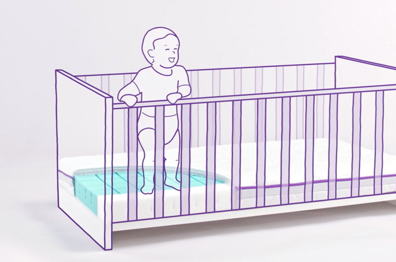Baby stands in a cot on a step.
