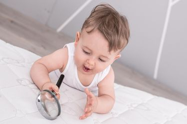 Baby is lying on a kids mattress and holding a magnifying glass.