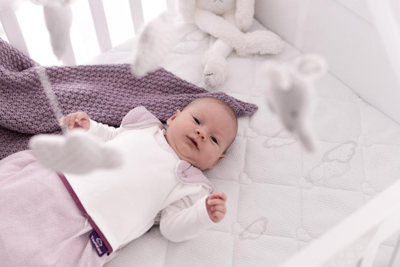 Baby with baby sleeping bag on baby mattress.
