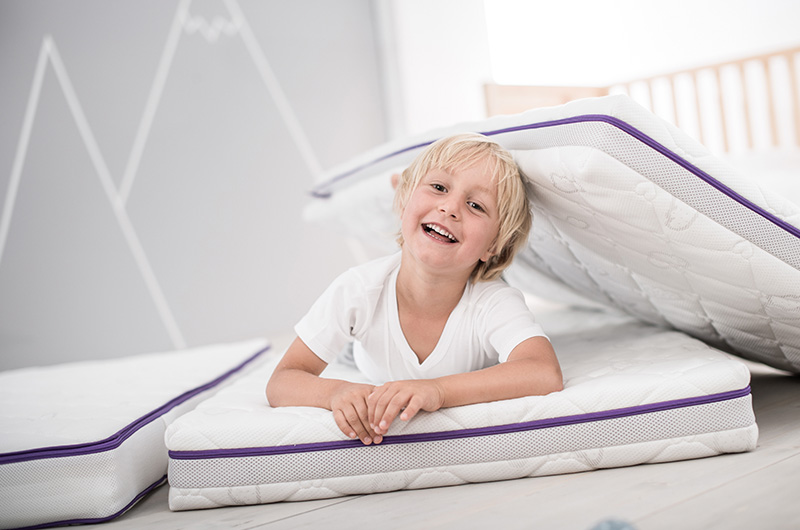 Girl is lying on dreaming kids mattress and smiling.