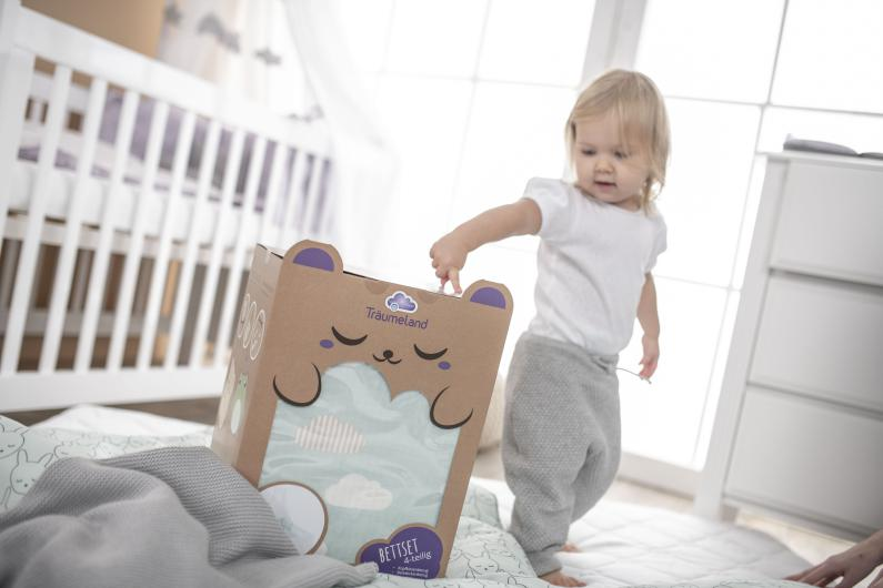 Smiling toddler is sitting on dreaming baby mattress.