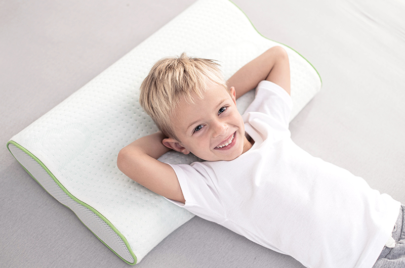 Smiling, little boy on children pillow