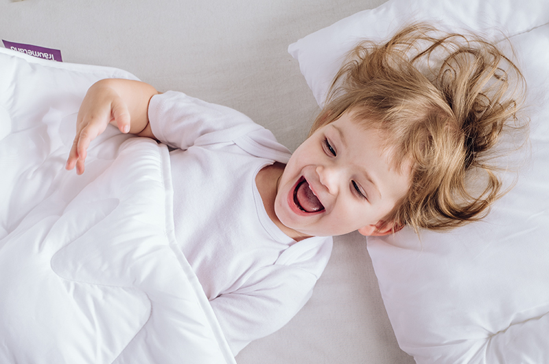 Little girl is having fun with dreaming blanket on travel mattress from dream land.