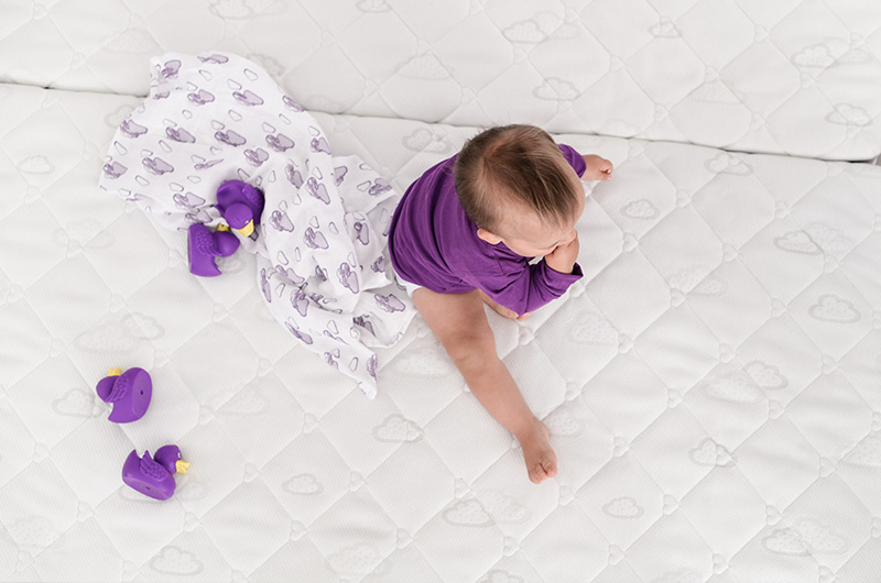 Content child on children mattress from Träumeland