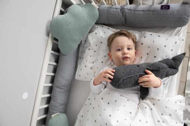 Chewing baby is sitting on dreaming baby mattress.
